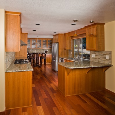a kitchen with wood flooring in a natural finish
